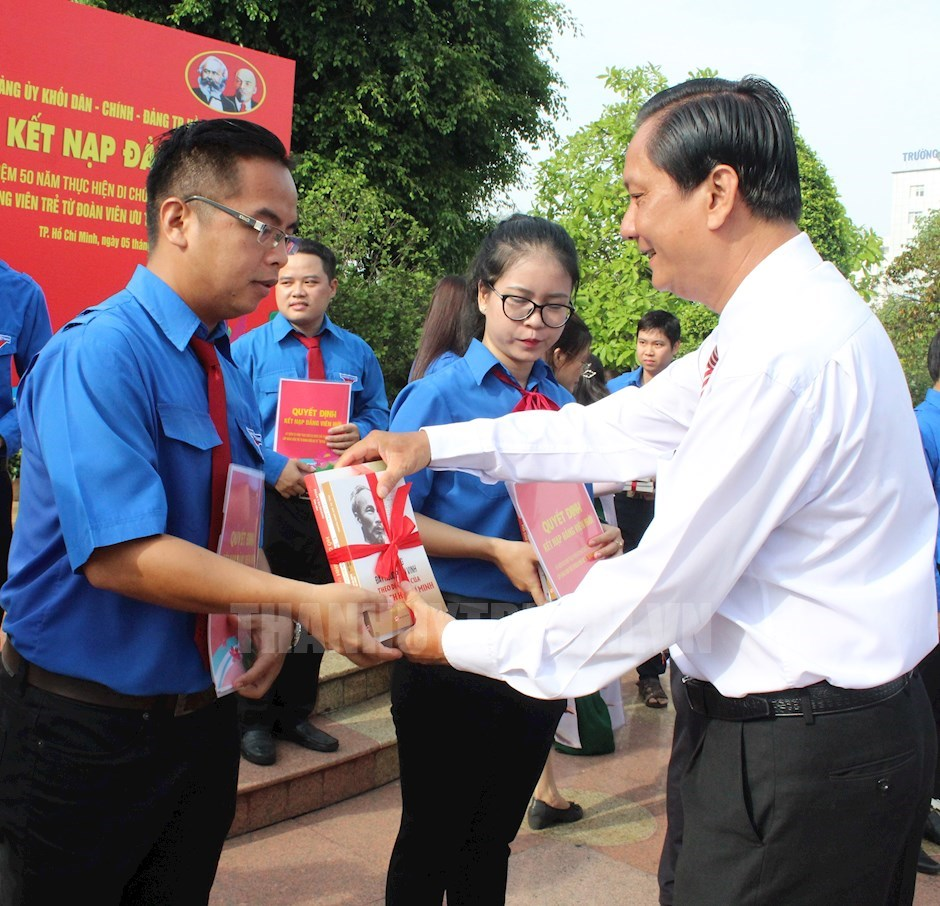 Phó Bí thư Đảng ủy Khối Dân - Chính - Đảng TPHCM Vũ Hữu Minh tặng quà cho các đảng viên mới