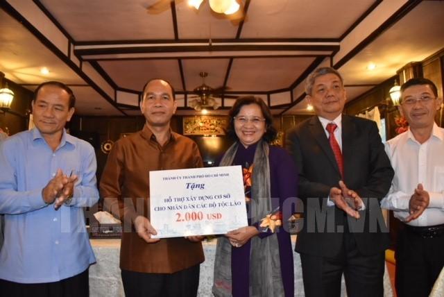 Đồng chí Thân Thị Thư trao quà ủng hộ các gia đình khó khăn của tỉnh Luang Phrabang.