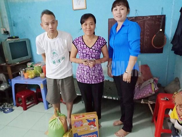 Chị Nguyễn Thị Minh Lâm (phải) tặng quà cho gia đình khó khăn.