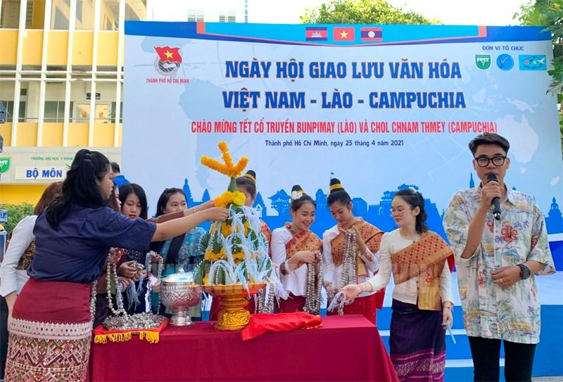 Các bạn sinh viên Việt Nam, Lào, Campuchia cùng giao lưu, tham gia nghi lễ buộc chỉ cổ tay.