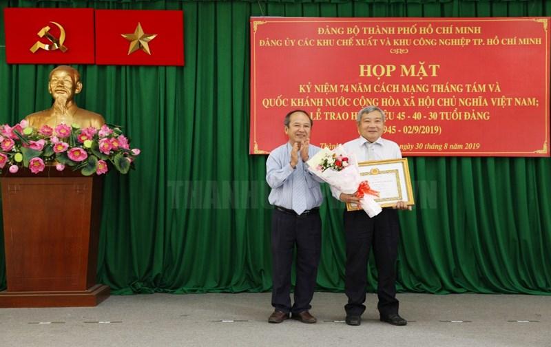 Thành ủy viên, Trưởng Ban Quản lý các Khu Chế xuất và Khu Công nghiệp TP Nguyễn Hoàng Năng trao Huy hiệu 40 năm tuổi Đảng cho đảng viên. (Ảnh: Minh Trí)