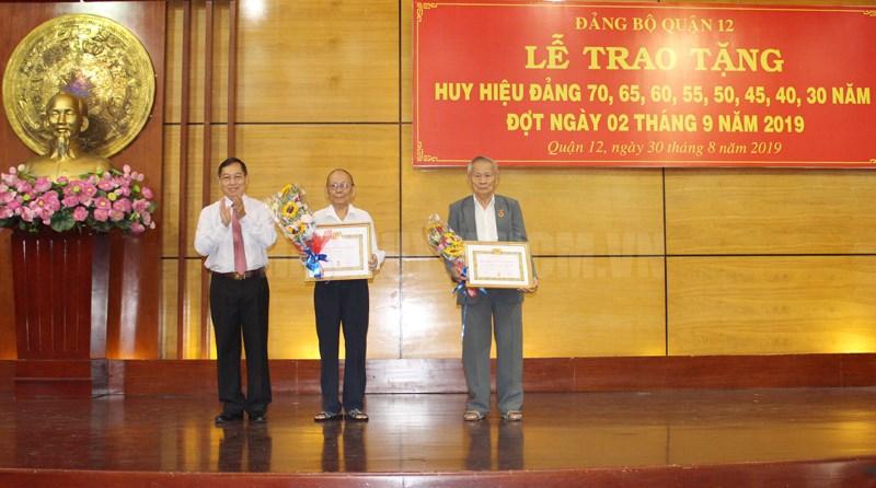 Đồng chí Trần Hữu Trí, Bí thư Quận ủy, Chủ tịch HĐND Quận 12 trao Huy hiệu Đảng cho đảng viên 70 năm tuổi Đảng. (Ảnh: Đoàn Nam)